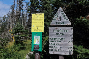 East Coast Trail sign at beginning of trail with various distances.