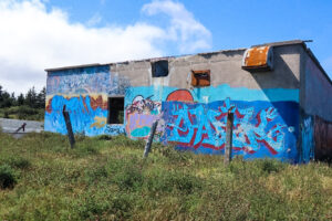 An abandoned concrete building covered in graffiti